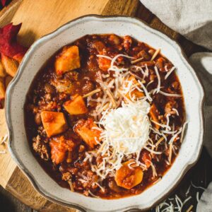 Sweet potato turkey chili with shredded cheese and sour cream on top in a bowl.