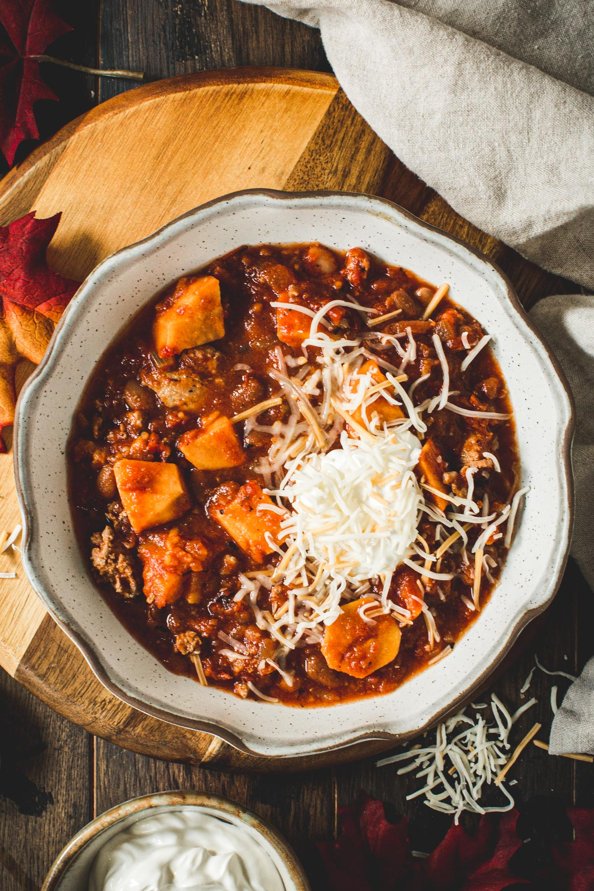 Crockpot sweet potato turkey chili topped with sour cream and shredded cheese.