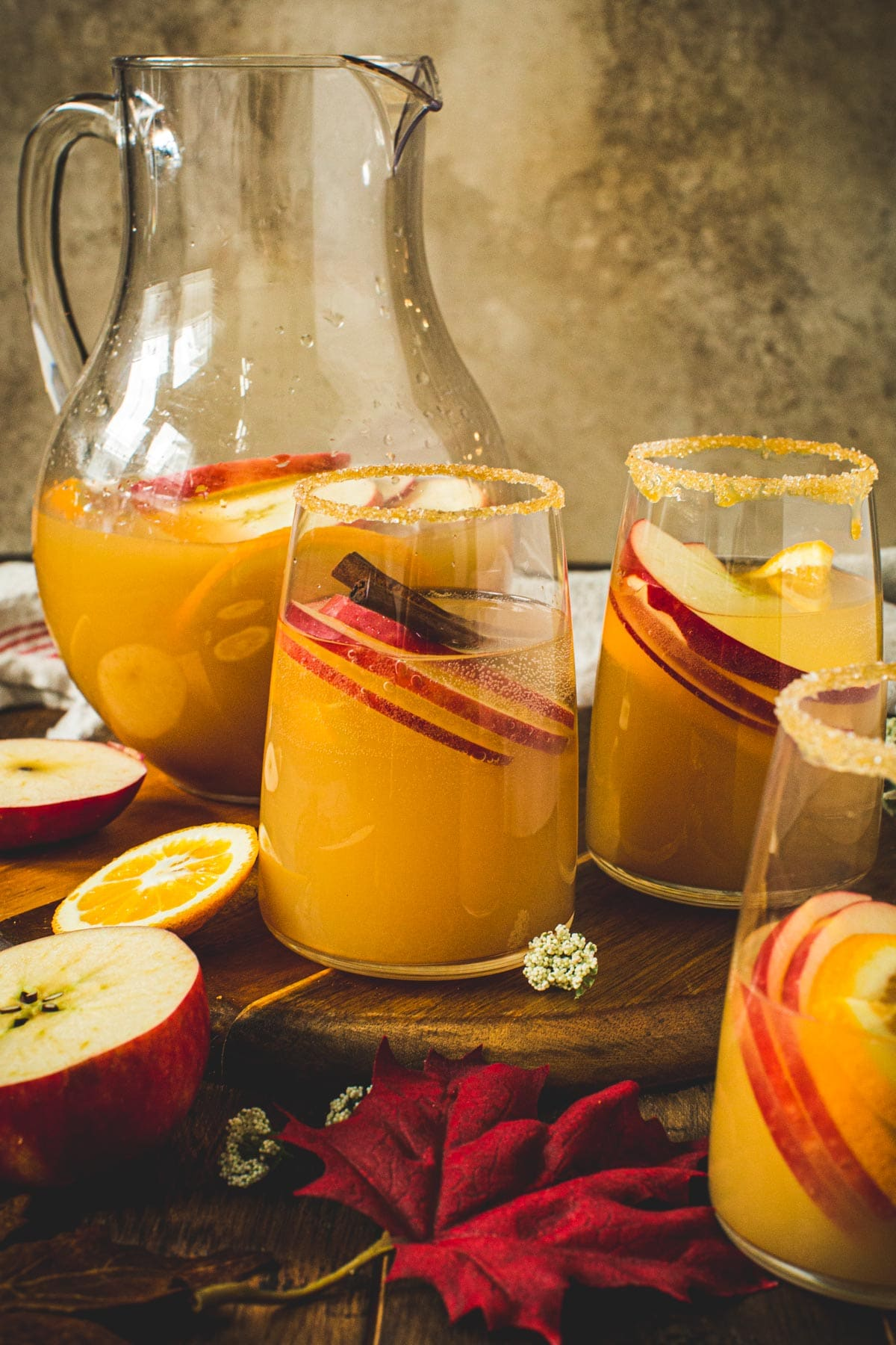 Three glasses filled with caramel apple sangria with a pitcher sitting behind.