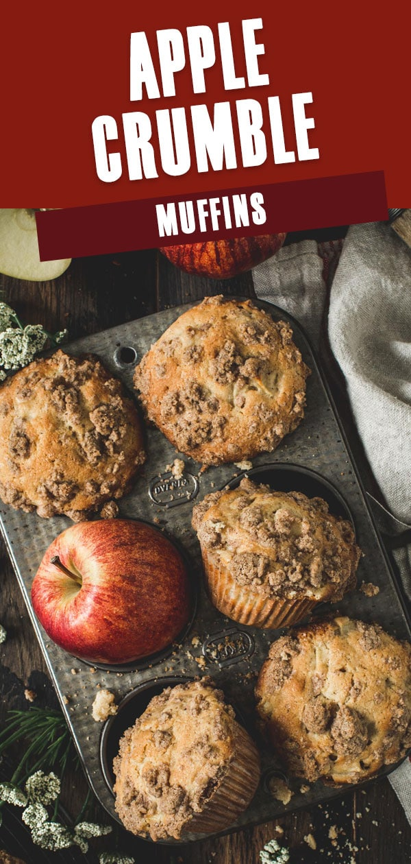 Apple crumble muffins in a muffin tin with apples surrounding.