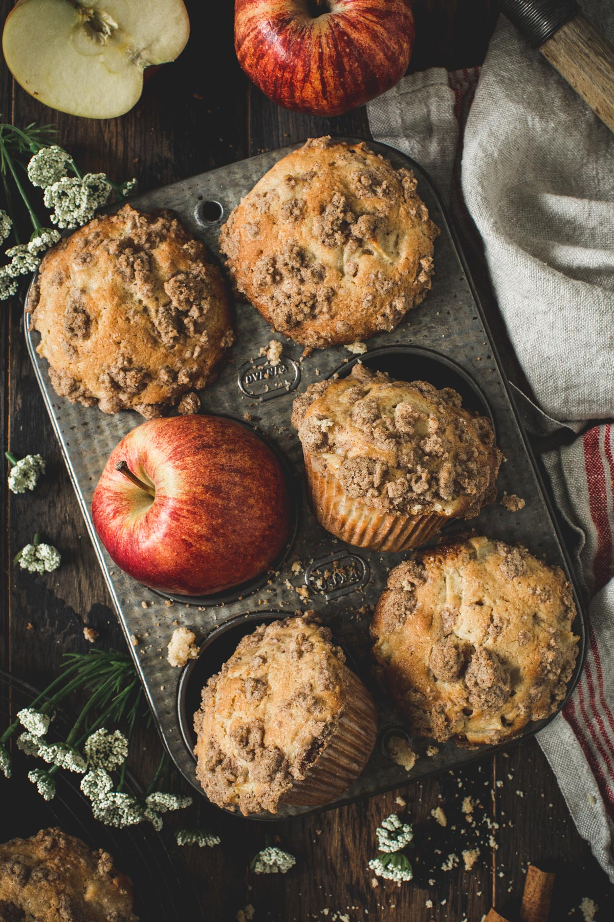 Apple crumble muffins in a muffin tin surrounded by crumbs.