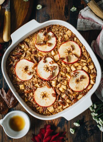 Baked apple oatmeal topped with pecans in a square baking dish.