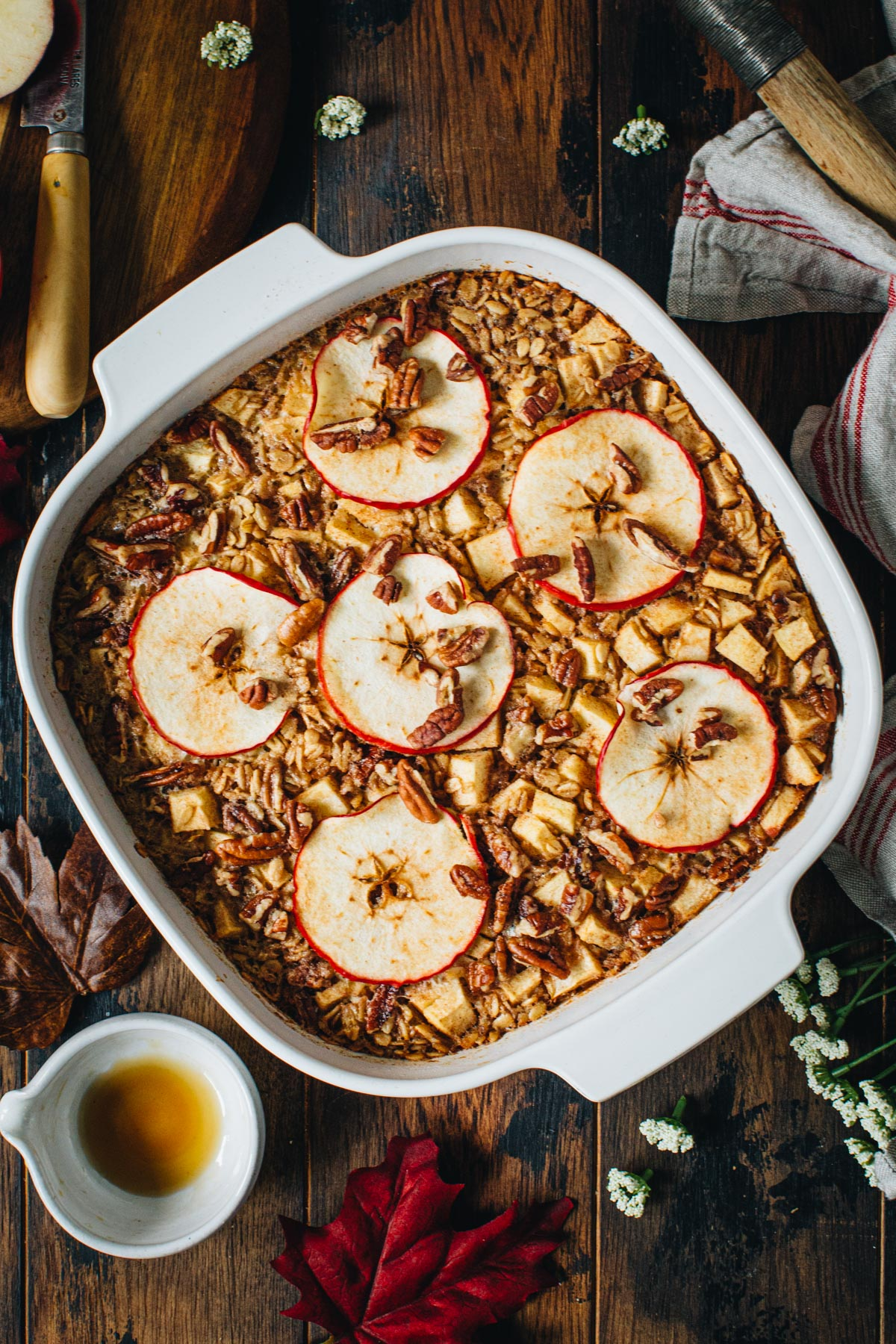 Baked apple oatmeal topped with pecans and apple slices in a square baking dish.