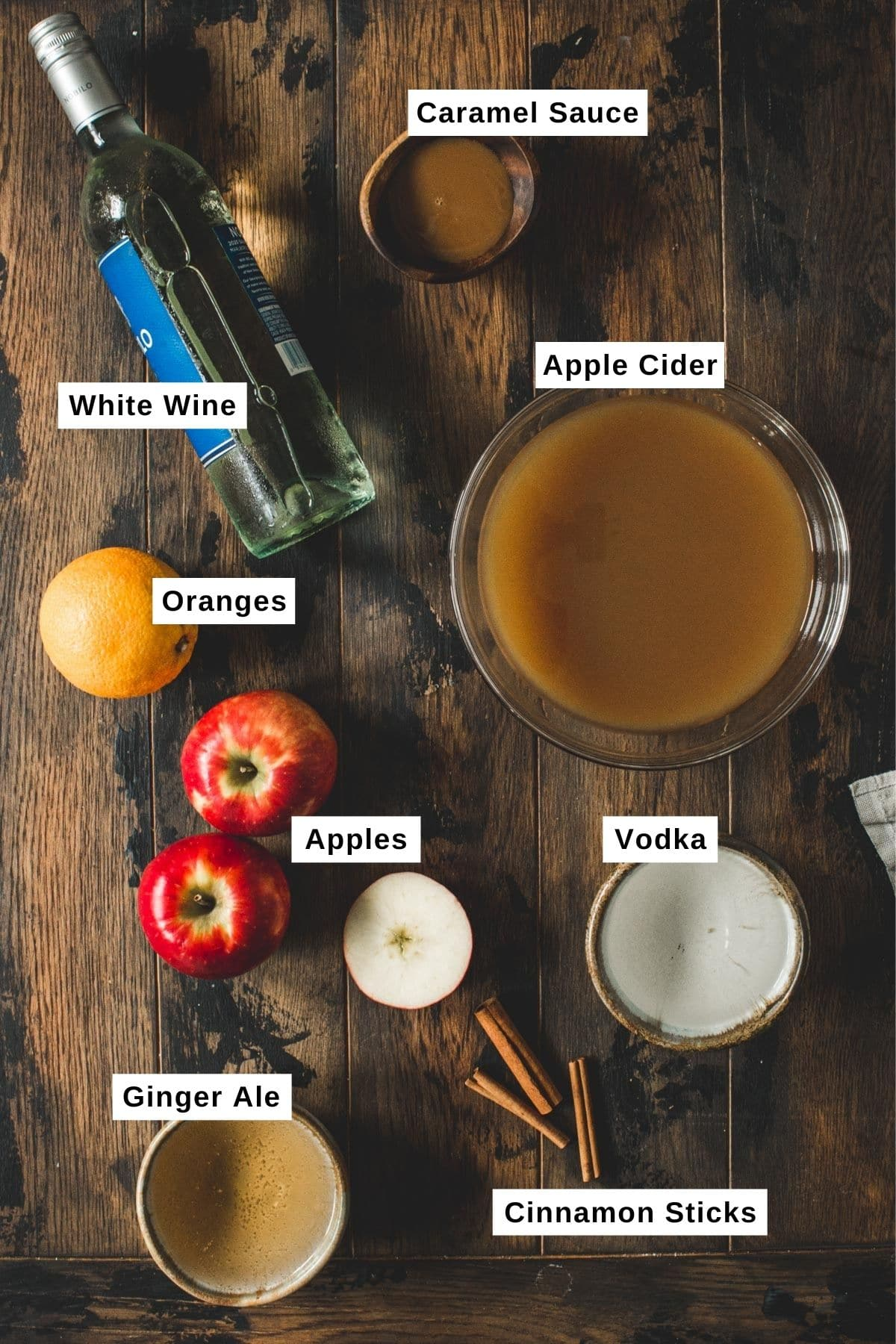 Caramel apple sangria ingredients on a wooden table.
