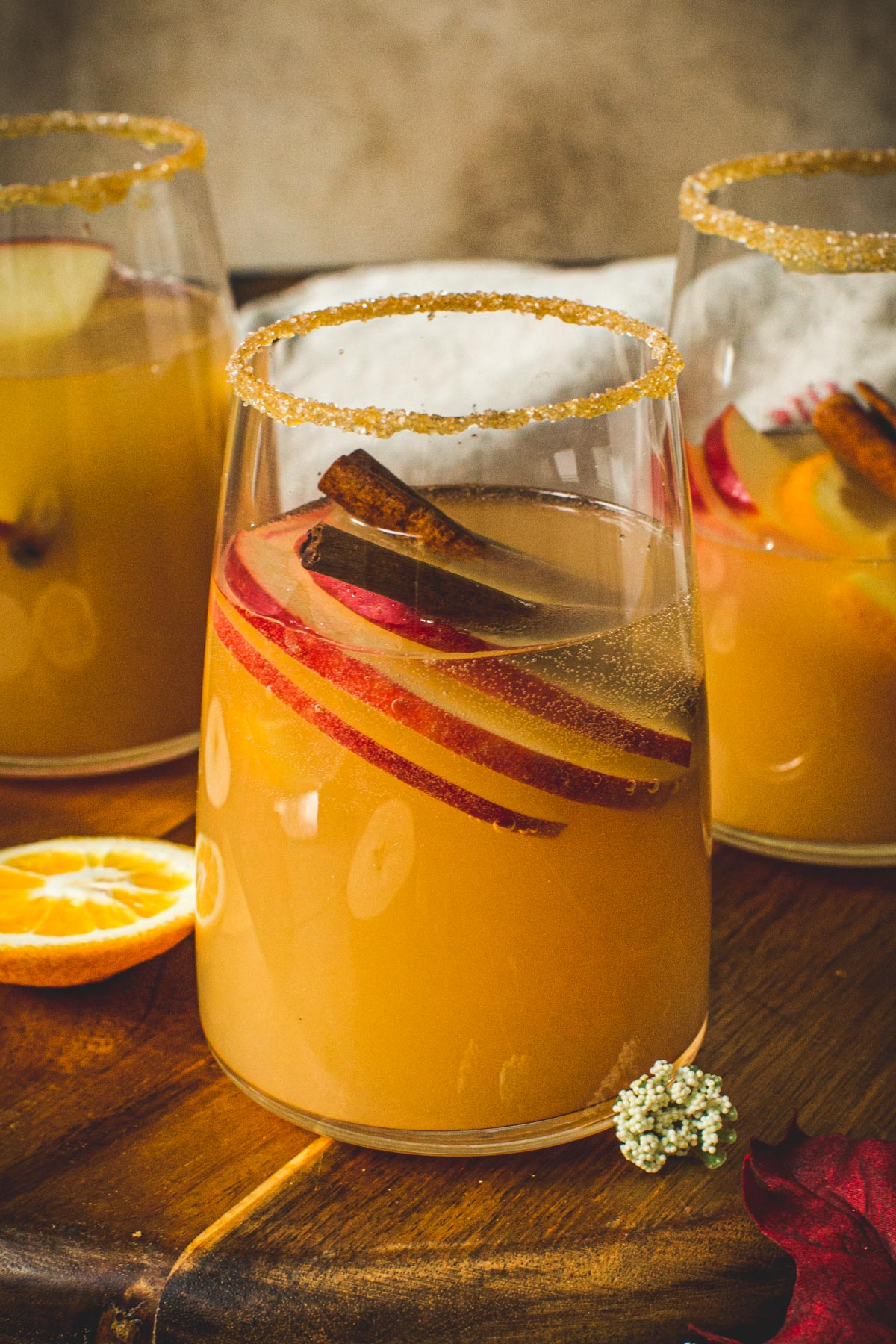 Caramel apple sangria in a glass with a caramel and sugar coated rim.