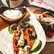Cheesesteak fajitas on a round board with sour cream and cheese in bowls behind.