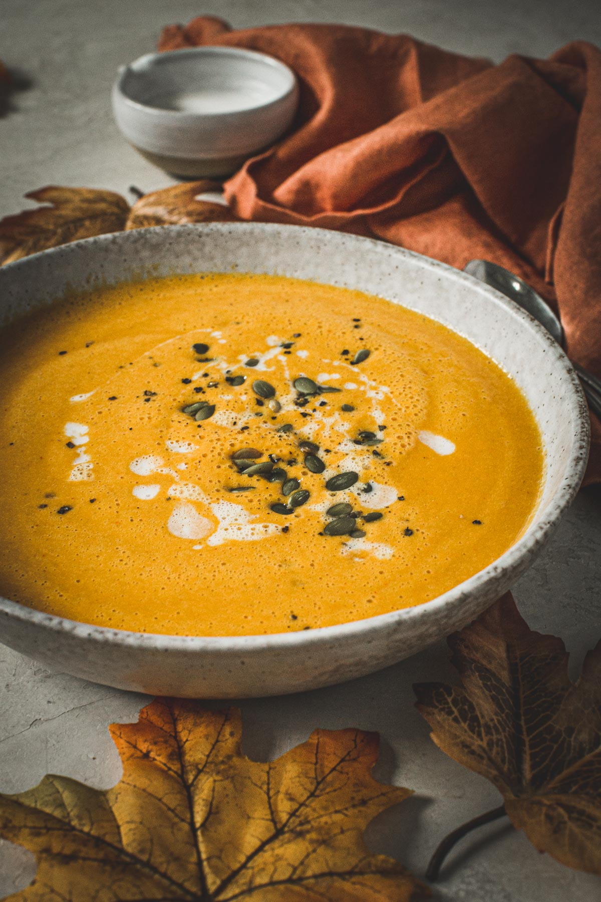 Curried pumpkin soup in a bowl topped with coconut milk and pumpkin seeds.