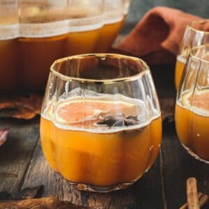 Pumpkin cocktail in a pumpkin-shaped glass with orange slices.