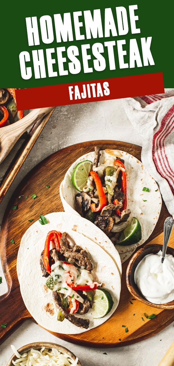 Homemade cheesesteak fajitas on a wooden board with sour cream next to it.