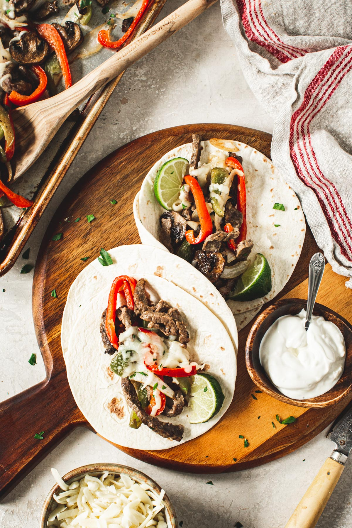 Homemade cheesesteak fajitas on a round wooden board with sour cream in a bowl beside it.