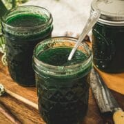 Jalapeno pepper jelly in a glass jar with a silver serving spoon.