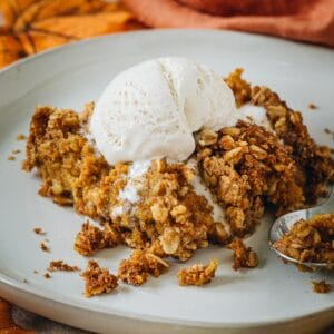 Pumpkin crisp topped with vanilla ice cream on a white plate.