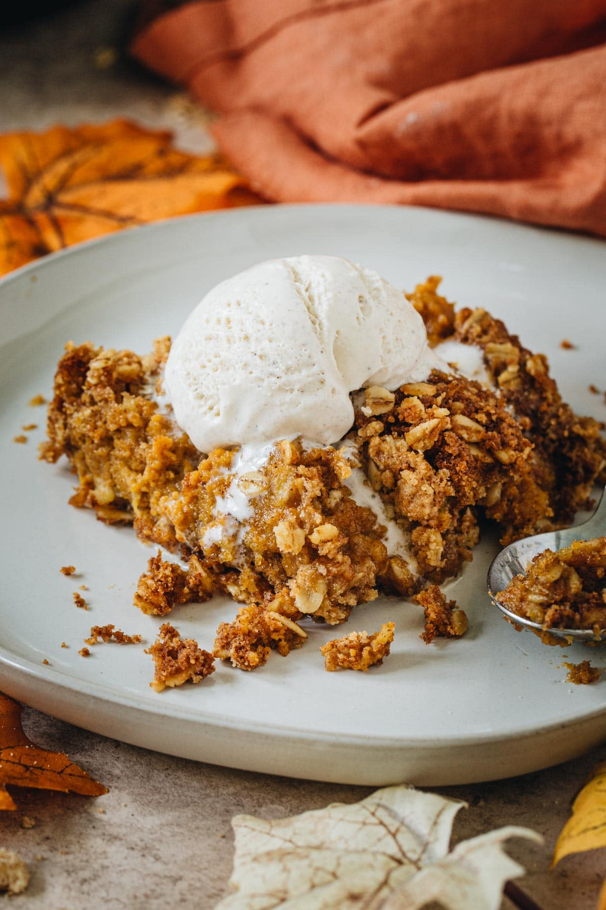 Pumpkin crisp topped with melting vanilla ice cream on a white plate.