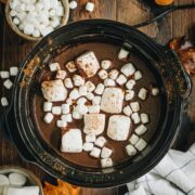 Pumpkin hot chocolate in a slow cooker topped with marshmallows.