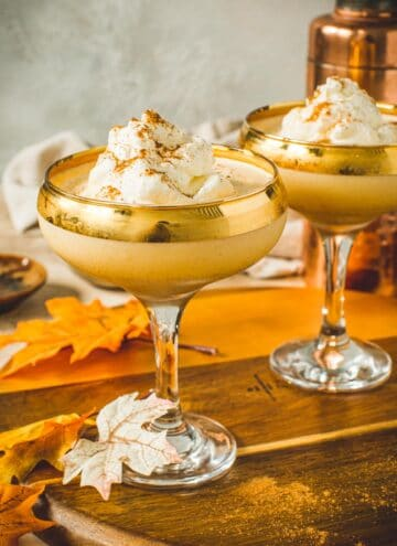 Pumpkin martini topped with whipped cream and cinnamon in a martini glass.