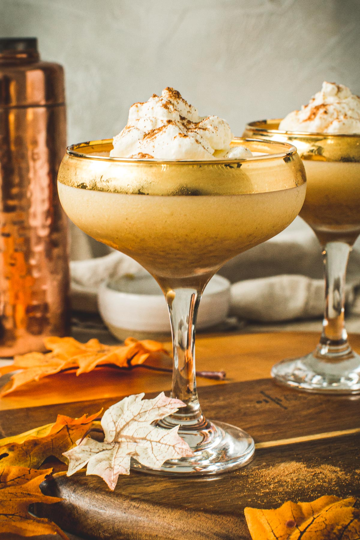 Pumpkin pie martini with whipped topping and cinnamon sprinkled on top in a martini glass.
