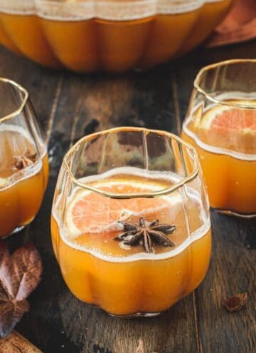 Pumpkin cocktail in a pumpkin-shaped glass topped with star anise and orange slices.
