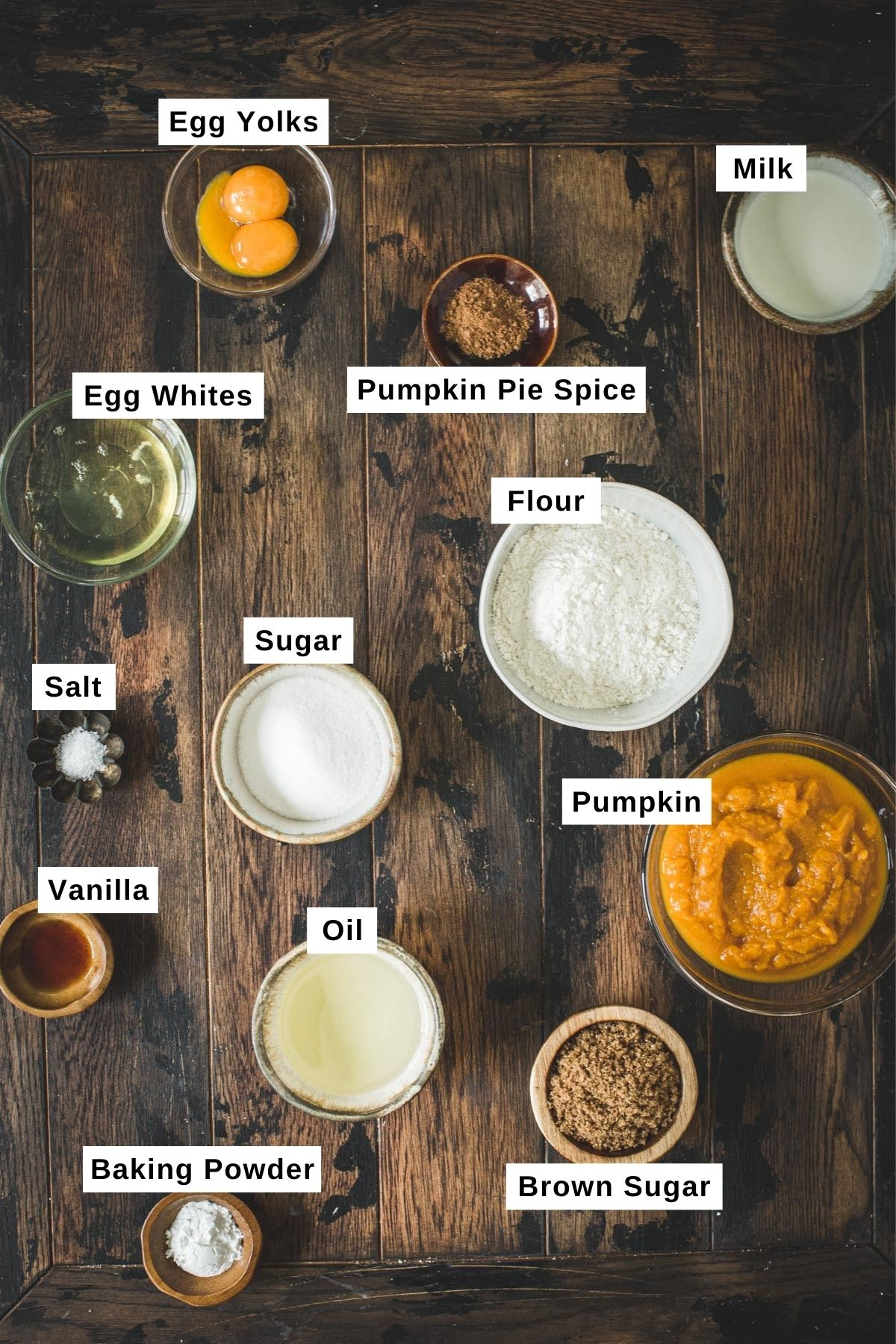Pumpkin spice waffles ingredients in bowls on a wooden table.