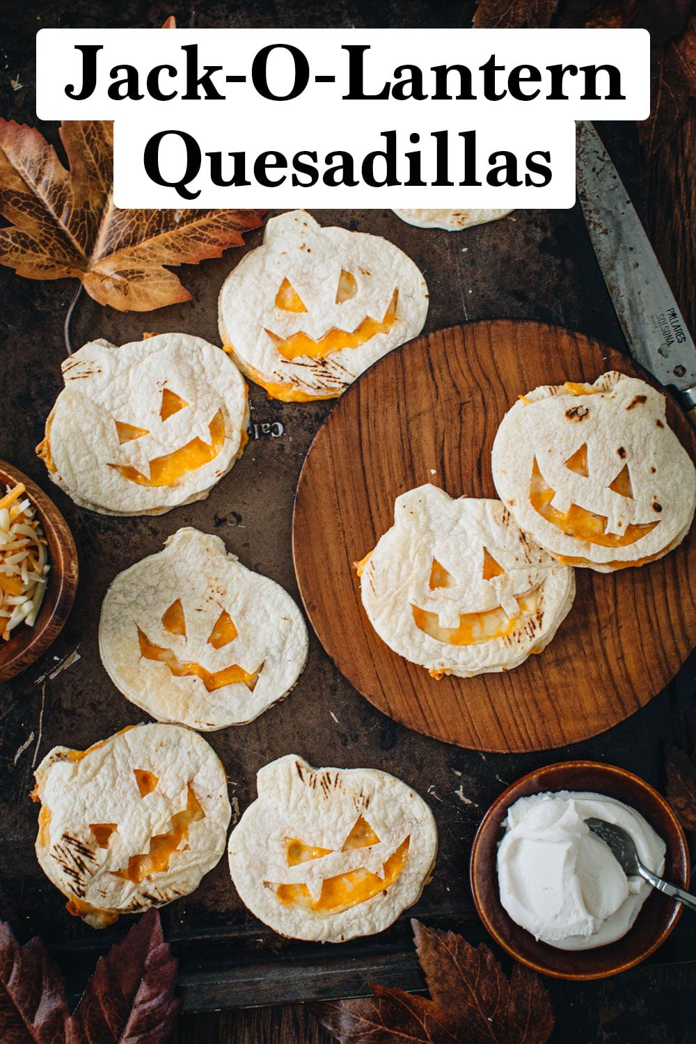 Jack-o-lantern quesadillas on a baking sheet and wooden plate.