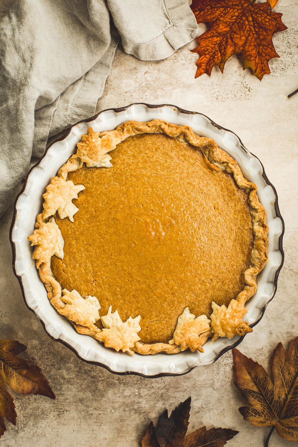Maple pumpkin pie with a leaf covered crust.