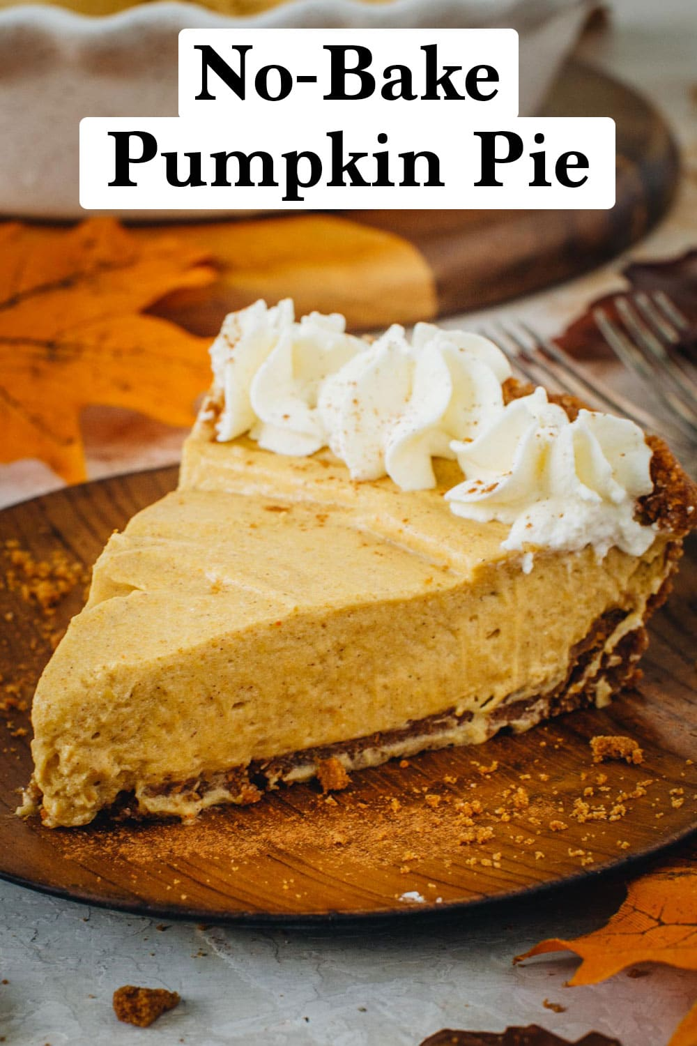 No-Bake Pumpkin Pie slice with whipped topping on a wooden plate.