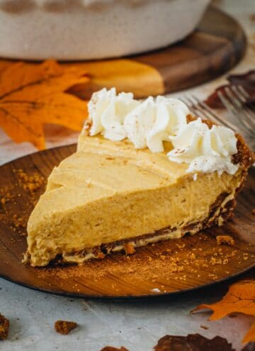 No-bake pumpkin pie slice with whipped cream on a wooden plate.