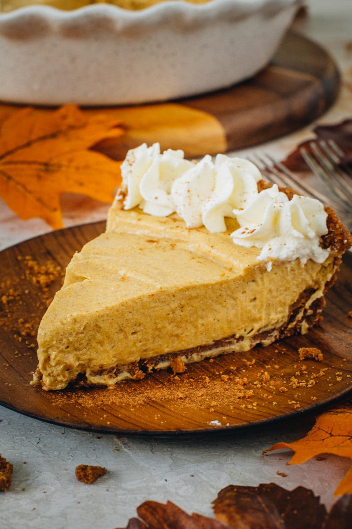 No-bake pumpkin pie with a graham cracker crust on a wooden plate.