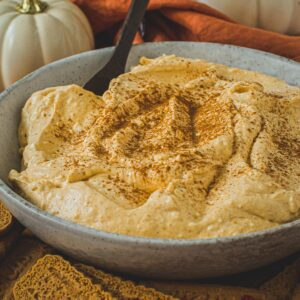 Pumpkin cheesecake dip topped with cinnamon and in a bowl.