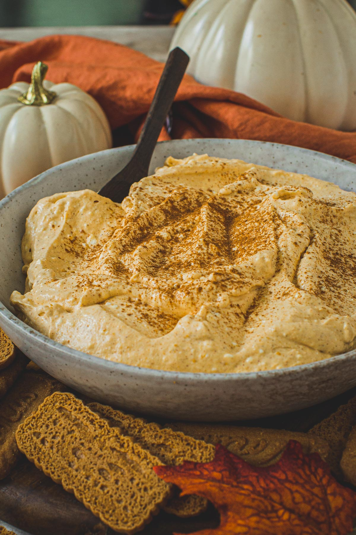 Pumpkin pie cheesecake dip topped with cinnamon in a bowl with a wooden spoon.