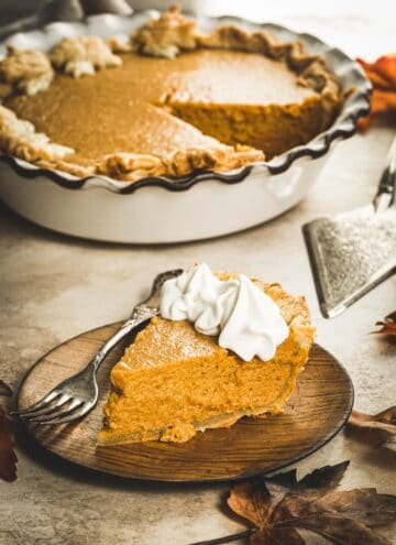 Slice of maple pumpkin pie with whipped cream on the edges.